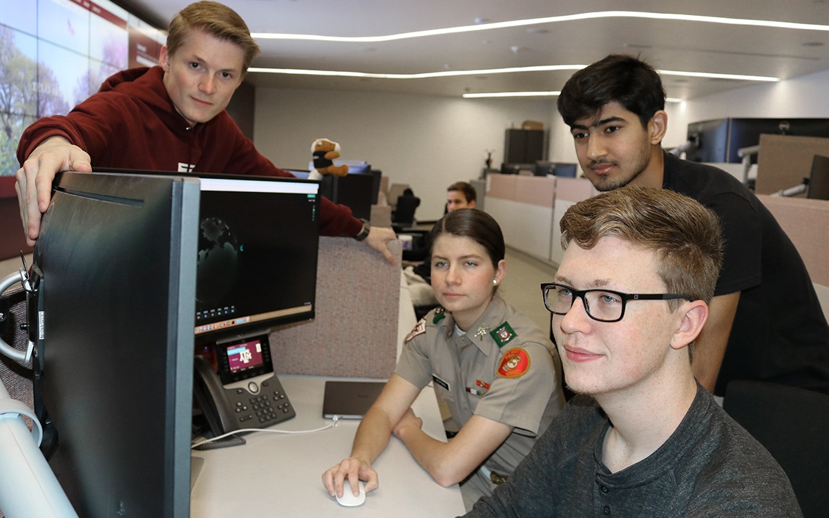 Students in the Cybersecurity Apprenticeship Program collaborate around a computer.